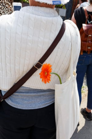 A gerbera peeks out of a tote bag
