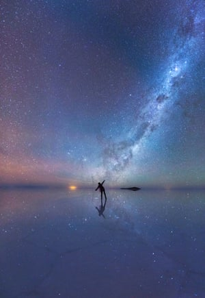 <strong>The Mirrored Night Sky</strong> An enthralled stargazer is immersed in the stars as the luminous purple sky is mirrored in the thin sheet of water across the world's largest salt flat, Salar de Uyuni, in Bolivia