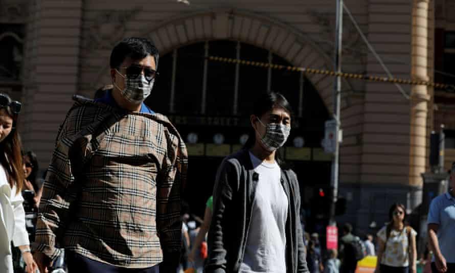 People wearing face masks walk by Flinders Street Station