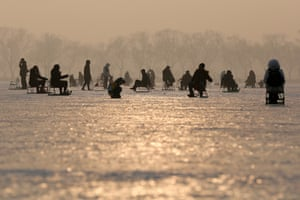 People sit on chairs outfitted with ice skates on the frozen surface of Kunming Lake in the Summer Palace.