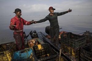 Crab fishermen whose clothing and equipment are soaked with oil take a smoke break on Lake Maracaibo, near Punta Gorda beach