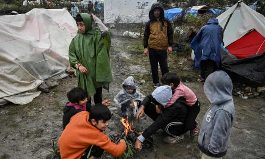 Children warm themselves around a camp fire in the refugee camp of Moria in Lesbos