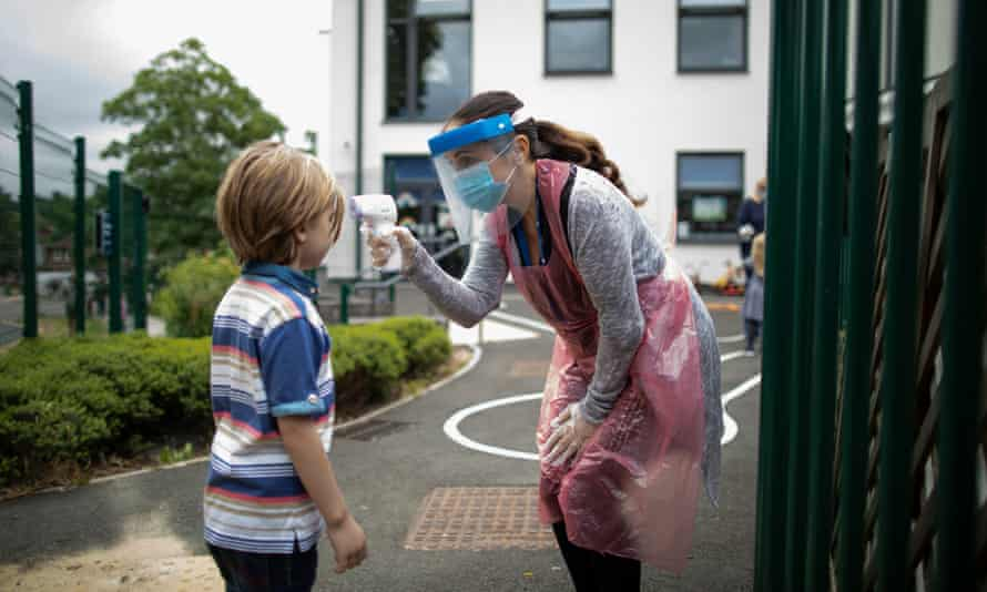 A member of staff wearing PPE takes a child's temperature at a school in London.