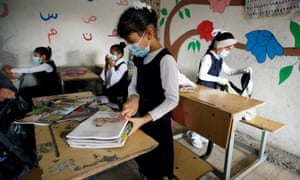Students arrange their books following the reopening of their school in Baghdad after months of closure due to the spread of coronavirus.