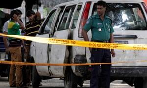 Bangladeshi police at the site where Cesare Tavella was shot in Dhaka