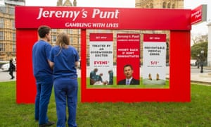Campaigners dressed as junior doctors with a fake betting shop storefront outside parliament