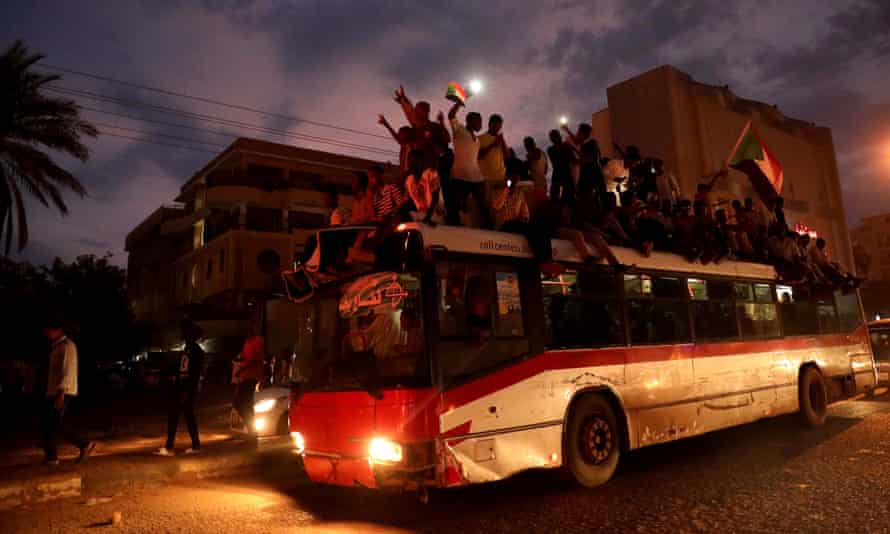 Sudanese people celebrate on top of a bus