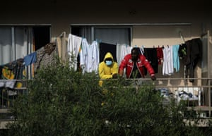 People stand on the balconies of a hotel-cum-refugee shelter quarantined after authorities found 150 cases of coronavirus