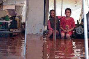 Two girls sit inside a flooded tent at the Mukhayyam al-Khair camp near the village of Kafr Uruq in the province of Idlib following heavy rain.