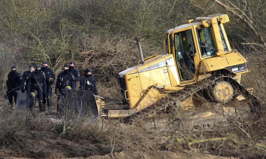 Police officers walk past a bulldozer in the Calais refugee camp, used to clear a 100m-long strip of land between the camp and the highway.