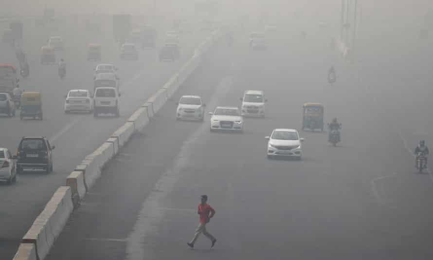 A man runs across an expressway cloaked in smog near Delhi.