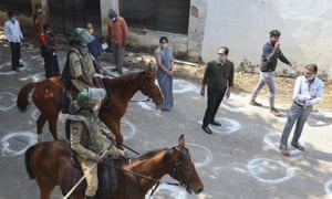 Security officers patrol on horses as Indians wearing face masks as a precaution against the coronavirus wait in a queue to cast their votes during the Greater Hyderabad Municipal Corporation elections in Hyderabad, India, Tuesday, 1 December, 2020.