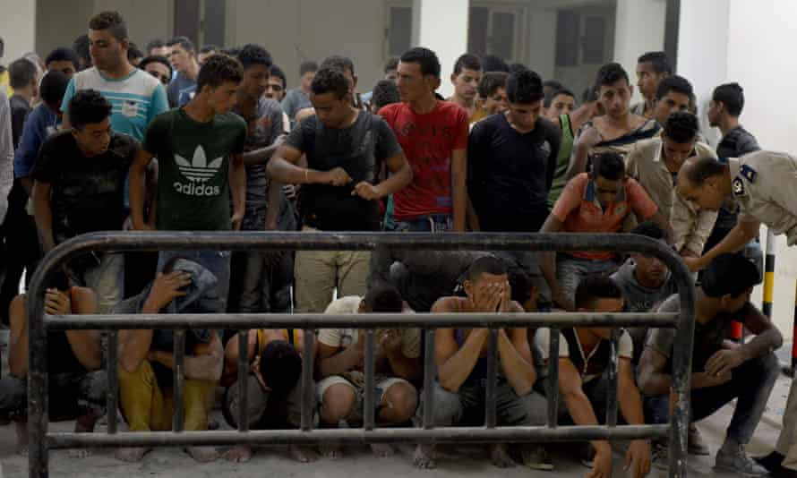 Young men put their heads in their hands after being rescued off the coast of Egypt