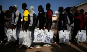 Gambian migrants returning home from Libya carry bags from UN agency the International Organization for Migration.