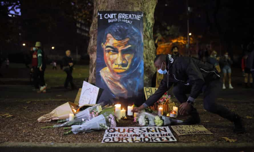 A man places a candle beneath a portrait of David Dungay during a protest against Aboriginal deaths in custody in Sydney last year. A NSW inquiry into Aboriginal deaths in custody has recommended sweeping reforms to the justice system.