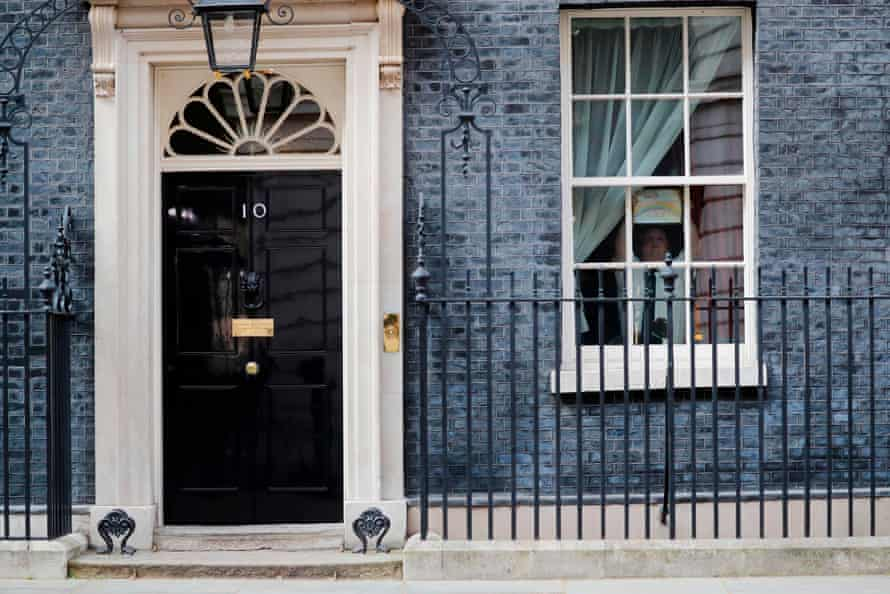 A member of staff sticks a poster of a rainbow on a window at 10 Downing Street last April, while Boris Johns is in hospital with coronavirus