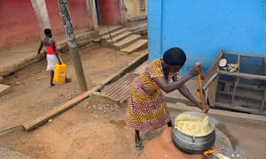 A woman prepares the West African dish fufu in the street with a large pestle and mortar.