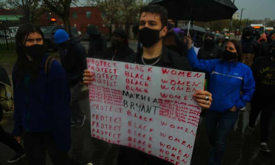 """戴着面具的示威者带有标志""""保护黑人妇女"""""""