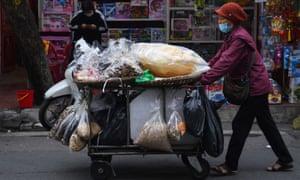 A street vendor pushes her cart full of dried goods in Hanoi on Thursday.