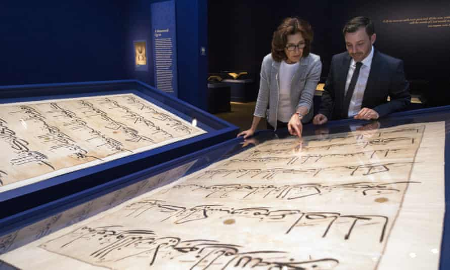 Massumeh Farhad, left, and Simon Rettig, curators of the exhibit, look at pages from a 5ft-by-7ft Qur'an displayed at the Sackler Gallery in Washington.