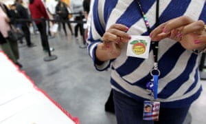 A voter shows off her sticker during early voting in Decatur, Georgia, on 22 October,