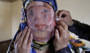 A woman dons a mask during the feast of La Diablada in Pillaro.