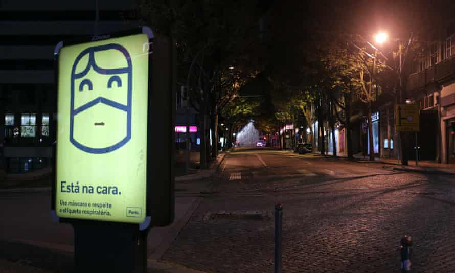 An empty street under streetlights at night, with an illuminated billboard in the foreground advising people to wear masks