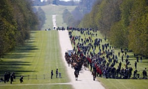 Onlookers watch the King's Troop Royal Horse Artillery arrive at the Long Walk