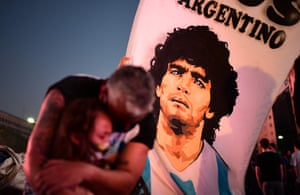A father and daughter mourn the death of Diego Maradona in Buenos Aires. A mile-long column of fans turned out to file past the casket of the Argentinian football star.