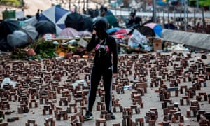 A protester stands amongst bricks placed on a barricaded street outside The Hong Kong Polytechnic University