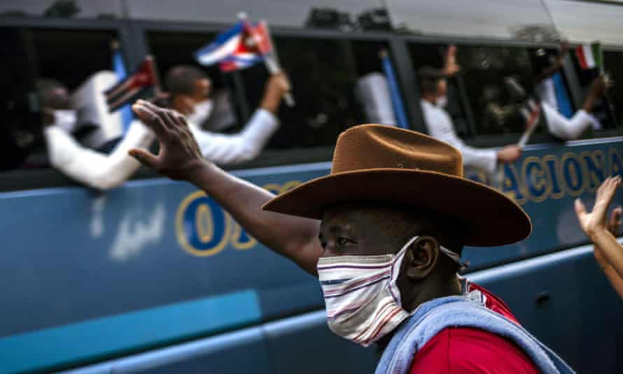 Man waves at doctors on a bus in Cuba
