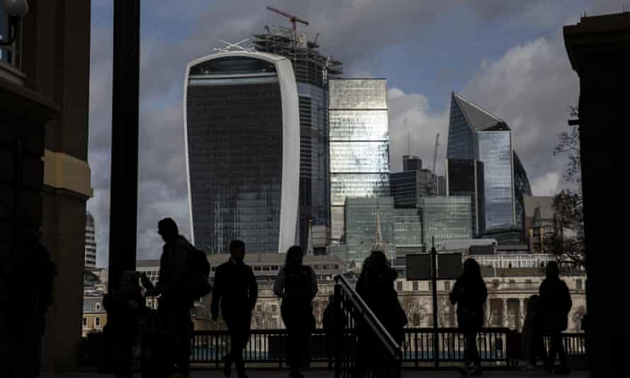 Members of the public walk past the city of London skyline