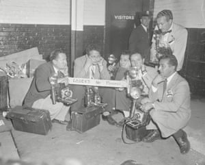 A group of photographers, who were assigned to the New York Yankees, sit forlornly outside of the losers' dressing room