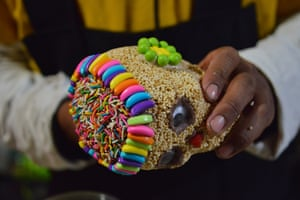 A candy factory worker decorates an amaranth skull for customers during the Día de Muertos celebrations