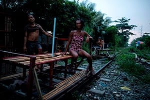 """trolley boy"" couple Tyson Aguha (L) and Joan Acebo waiting for passengers along a train track in Manila."