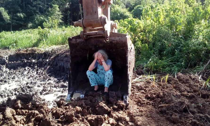 Joannah Stutchbury sitting in the scoop of a digger