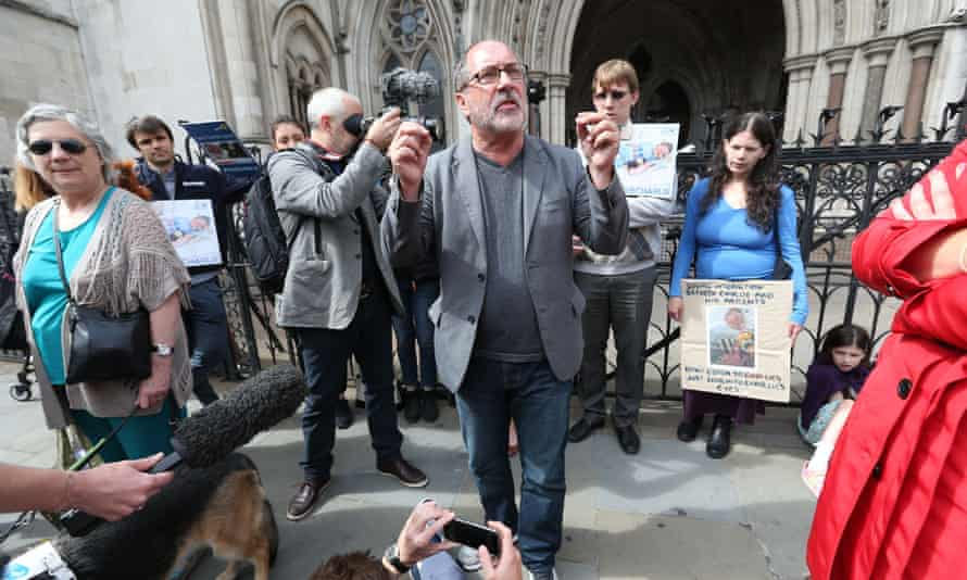 A small group of activists including a US cleric supporting Charlie Gard's parent hold a prayer vigil outside the high court in London on Sunday.