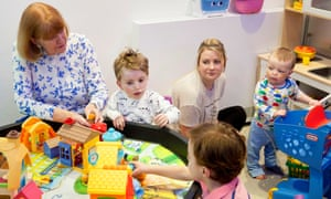 Oliver and Freddie, both 2, with their family in the playroom.