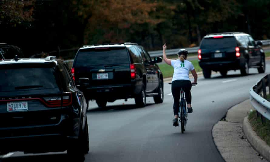 Juli Briskman giving the middle finger to Trump's motorcade while riding a bike in 2017.