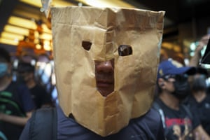 A protester uses a paper bag as a mask.