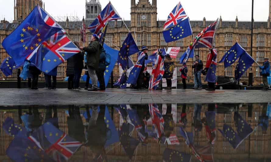 Anti-Brexit demonstrators wave Union and EU flags as they protest opposite the Houses of Parliament in London .