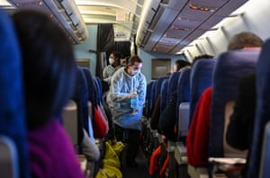 A crew member of an evacuation flight of French citizens from Wuhan gives passengers disinfectant during the flight to France on February 1, 2020, as they are repatriated from the coronavirus hot zone