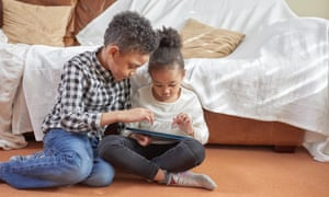 Two children (models) using a tablet device
