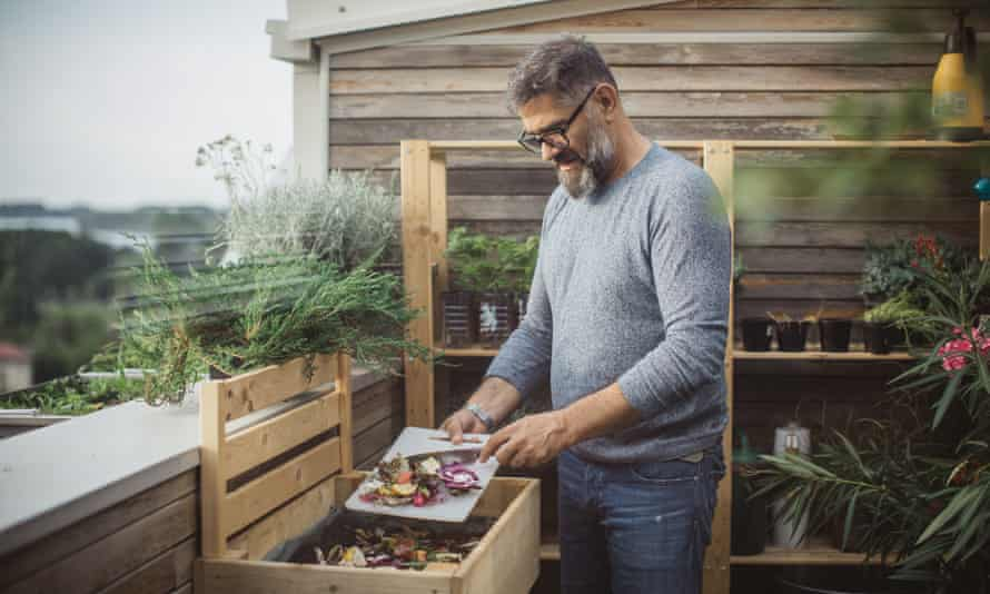 A man scraping vegetables into a compost bin on his balcony
