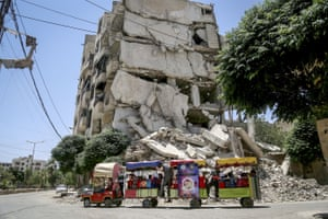 A train goes past collapsed buildings near the children's park in Damascus opened during Eid al-Fitr