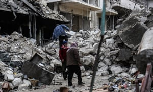 Locals inspect damaged buildings after Russian warplanes hit residential areas in Idlib