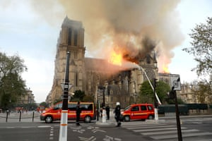 Firefighters douse the cathedral with water from hoses.