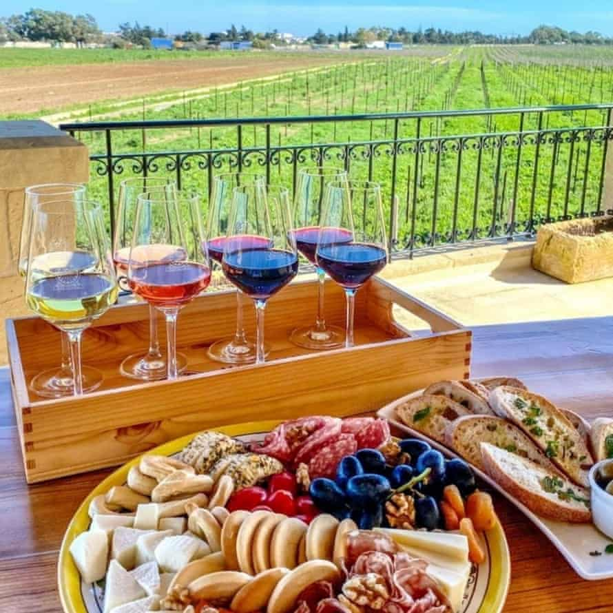 View of wines and meats on a table in front of the vines at Meridiana Wine Estate, Malta.