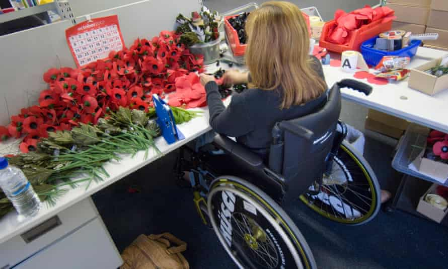 Disabled poppy maker works from her wheelchair at the British Legion Poppy factory in Surrey