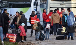 Migrants wait to board buses to leave the Calais camp